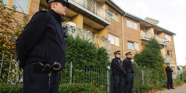 Police officers stand outside flats in Brixton, south London, as police are conducting house-to-house...