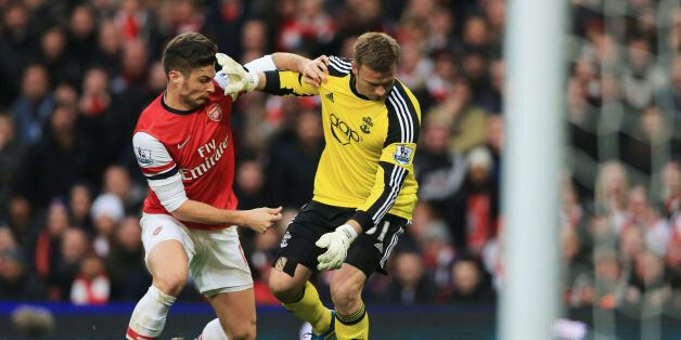 Arsenal's Olivier Giroud (left) challeges Southampton's Artur Boruc to then go on and score during the...