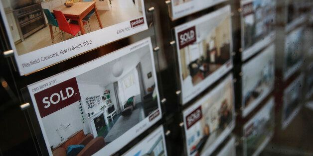 'Sold' signs sits on photographs of a residential properties in an estate agent's window display in London,...