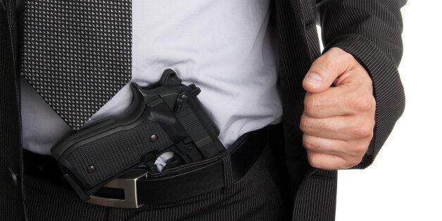 man in suit showing gun