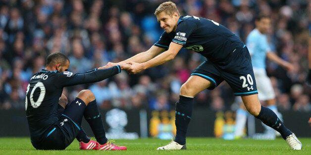 MANCHESTER, ENGLAND - NOVEMBER 24: Michael Dawson of Tottenham Hotspur helps Sandro to his feet during...