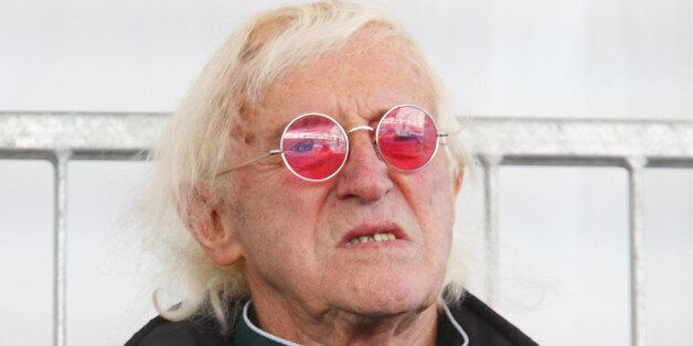 Sir Jimmy Savile watches as Britain's Queen Elizabeth II names Cunard's newest cruise ship, the Queen...