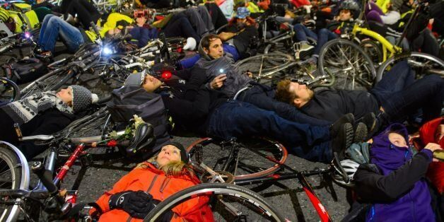 Cyclists take part in a 'die-in' protest outside the headquarters of Transport for