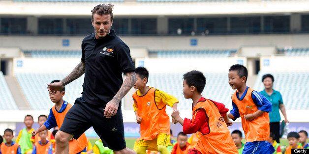 NANJING, CHINA - JUNE 18: (CHINA OUT) David Beckham plays football with children at at Nanjing Olympic...