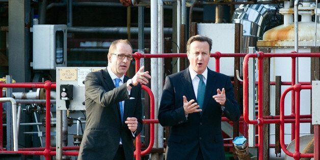 British Prime Minister David Cameron (R) talks with CEO of GlaxoSmithKline Andrew Witty during a visit...