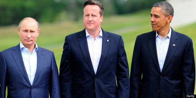 Britain's Prime Minister David Cameron (C) stands planked by Russia's President Vladimir Putin (L) and...