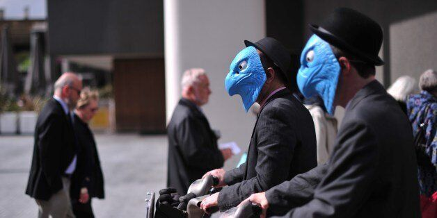 Protesters wearing masks in a satirical rendering of the eagle emblem of Barclay's Bank stage a demonstration...