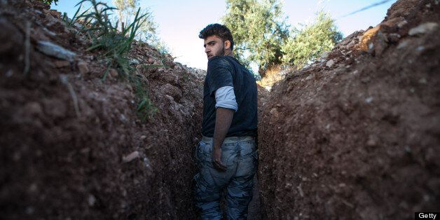 A Syrian rebel fighter throughout a trench dig by the rebels to hold a position, 100m far from the regime-controlled...