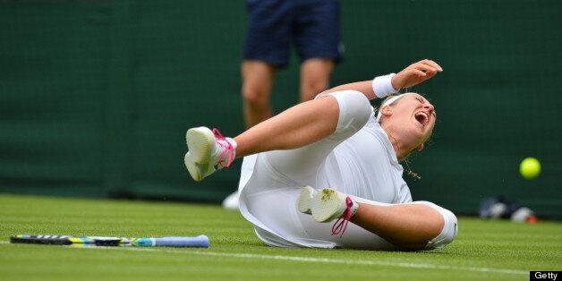 Belarus's Victoria Azarenka falls on court during a point against Portugal's Maria Joao Kohler during...