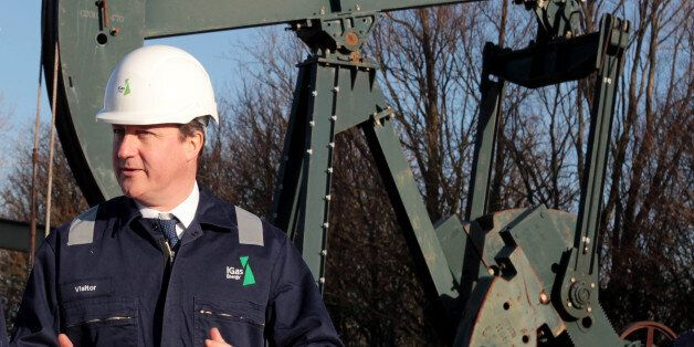 Prime Minister David Cameron looks on during a guided tour of the IGas shale drilling plant oil depot...