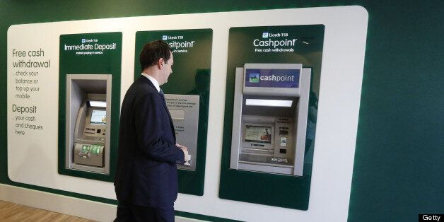 Britain's Chancellor of the Exchequer George Osborne approaches a cash machine at a brank of Lloyds TSB...