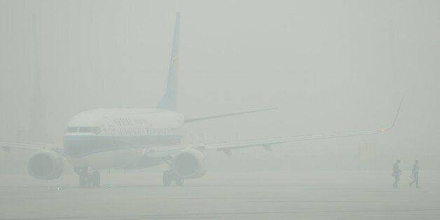 An aircraft is barely visible through thick smog on the tarmac of Hongqiao airport in Shanghai as severe...