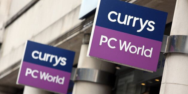 Signs hang above the entrance to a Currys PC World store, operated by Dixons Retail Plc, in London, U.K.,...