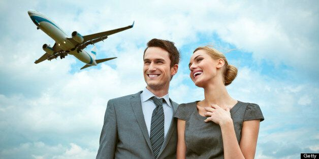 Outdoor portrait of business couple with flying airplane in the
