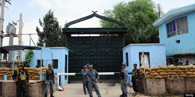 Afghan policemen stand guard at the gate of the main prison in