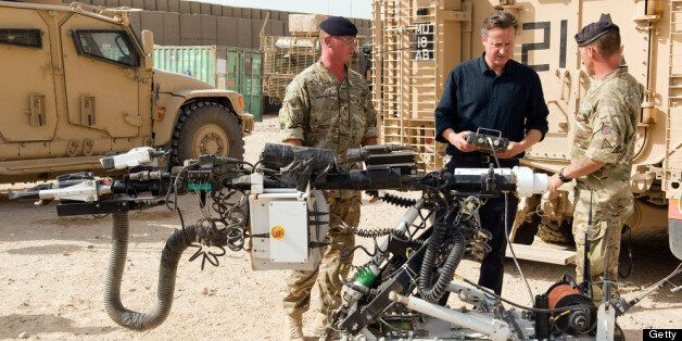 CAMP BASTION, AFGHANISTAN - JUNE 29: British Prime Minister David Cameron (C) is shown a remote-controlled...