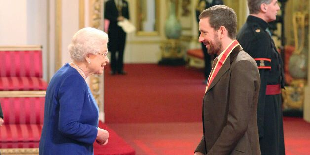 Sir Bradley Wiggins is knighted by Queen Elizabeth II at Buckingham Palace, central