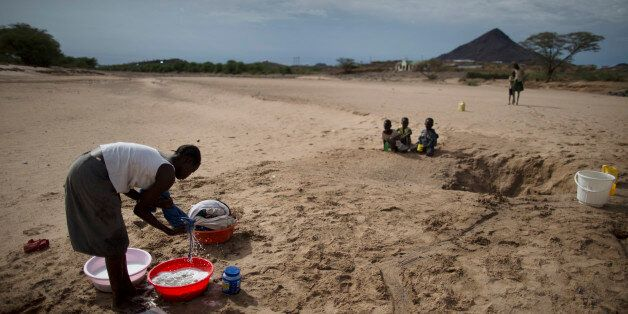 A Turkana woman washes clothes using water she scooped from a dry river bed in Lodwar (Turkana region)...