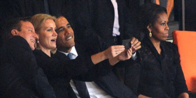 President Barack Obama (R) and British Prime Minister David Cameron pose for a selfie picture with Denmark's...