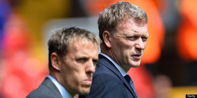 Everton's English defender Phil Neville (L) stands with manager David Moyes before the start of the English...