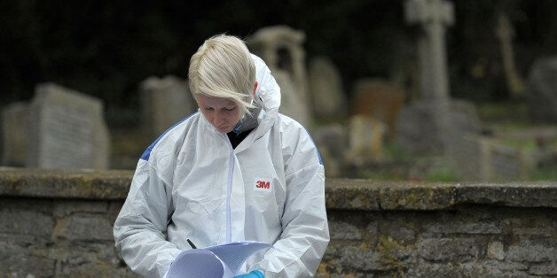 A Forensic officer at the scene at Great Western Cemetery by All Saints' Church in Didcot, Oxfordshire,...