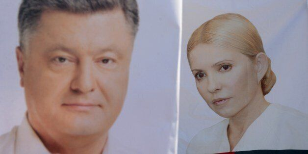 Placards depecting presidential candidates Yulia Tymoshenko (R) and Petro Poroshenko (L) are pictured...