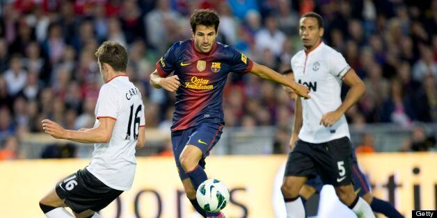 Cesc Fabregas (C) of Barcelona vies for the ball with Michael Carrick (L) and Rio Ferdinand (R) of Manchester...