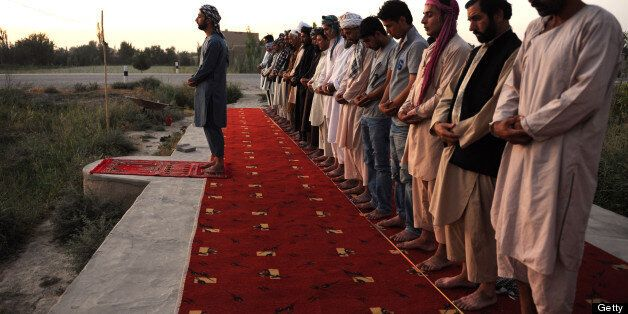 Afghan men pray in an open area during the holy month of Ramadan on the outskirts of Mazar-i Sharif on...
