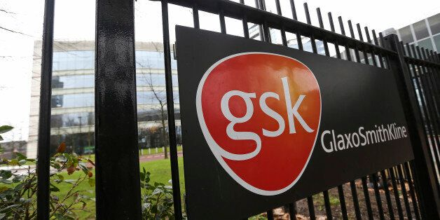 A logo sits on a metal security gate outside GlaxoSmithKline Plc's headquarters in London, U.K., on Wednesday,...
