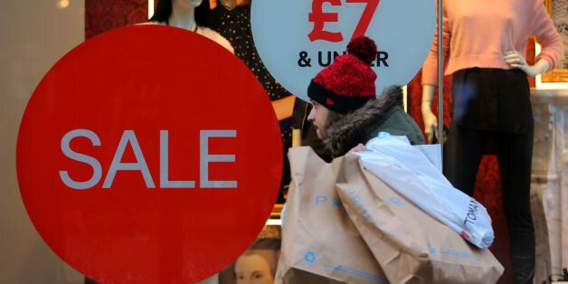 A shop on Market Street in Manchester advertises its sale, as shoppers buy last minute items before Christmas