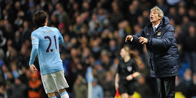 MANCHESTER, ENGLAND - DECEMBER 28: Manchester City Manager Manuel Pellegrini issues orders to David Silva...