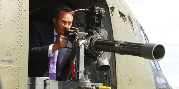 Defence Secretary Dr Liam Fox looks through the sights of a machine gun aboard a Chinook helicopter at...