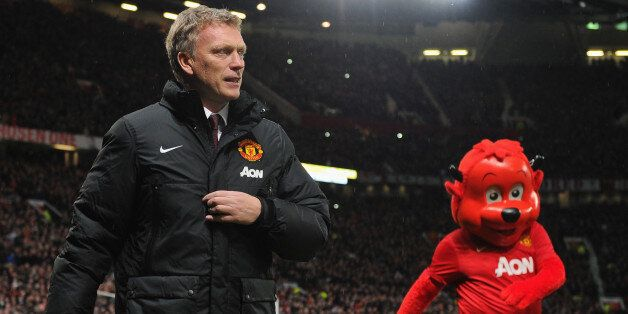 MANCHESTER, ENGLAND - JANUARY 01: Manchester United Manager David Moyes walks with mascot Fred the Red...