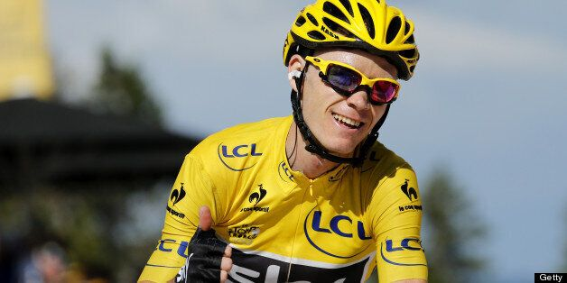 Stage's third placed overall leader's yellow jersey Britain's Christopher Froome thumbs up as he crosses...