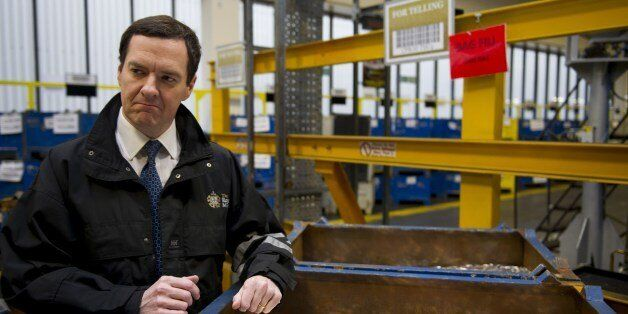Britain's Chancellor of the Exchequer George Osborne holds freshly minted coins during a visit to the...