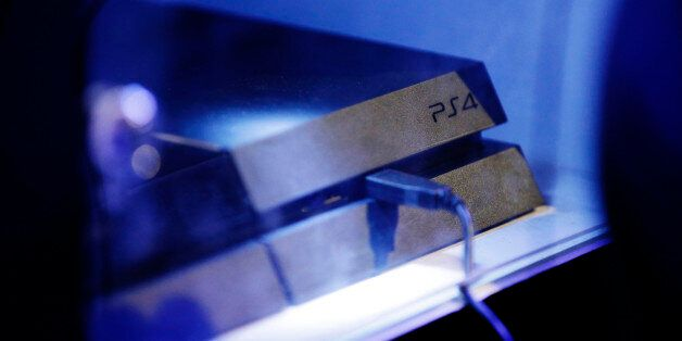 A logo sits above a USB cable attached to a PlayStation 4 (PS4) games console, manufactured by Sony Corp.,...