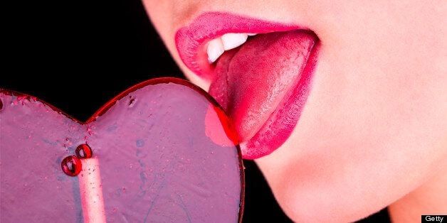 Girl licks heart lollipop on black background