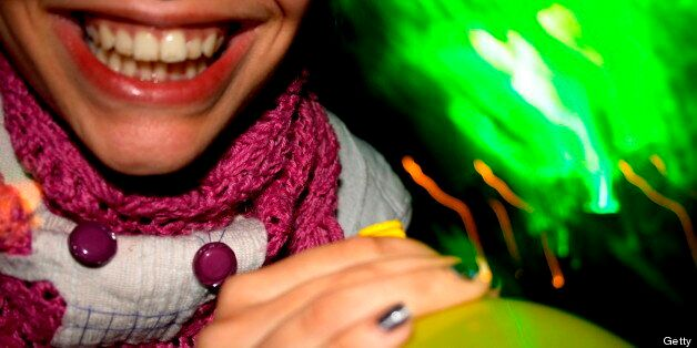 Detail of someone smiling and holding a laughing gas balloon. (Photo by Universal Images Group via Getty