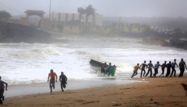 People try to pull back a fishing boat that was carries away by waves on the Arabian Sea coast as others...