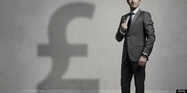 Businessman with a big Pound Sterling shadow. Success concept. Grain is