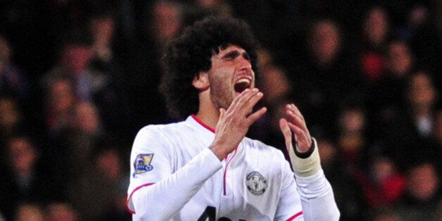 Manchester United's Belgian midfielder Marouane Fellaini reacts after missing a chance during the English...