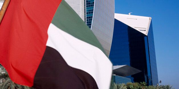 UAE, Dubai, national bank of Dubai seen from dhow on Dubai creek with UAE flag in the