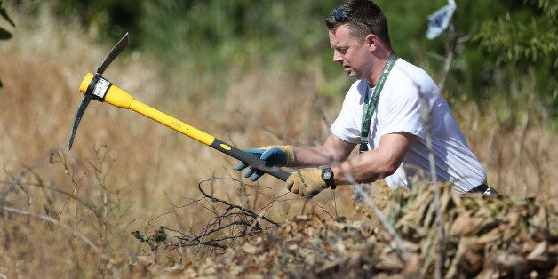 A British police officer clears an area of wasteland during the search for evidence of Madeleine McCann,...