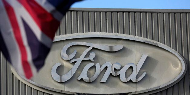 A Ford logo is seen on a stamping operations building near a Union Jack flag at the Ford Motor Co. automobile...