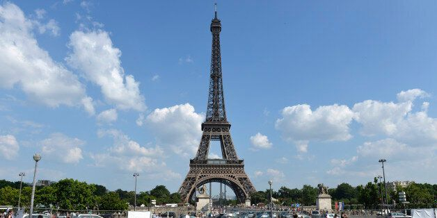 Children play in a fountain while people enjoy the sun in front of the Eiffel Tower on July 7, 2013 in...