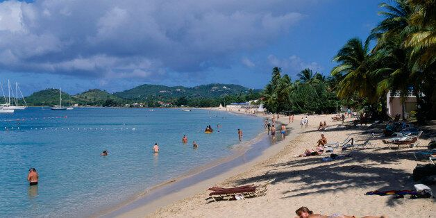WEST INDIES St Lucia Reduit Beach Sunbathers and swimmers on sandy beach lined with palm trees. Yachts...