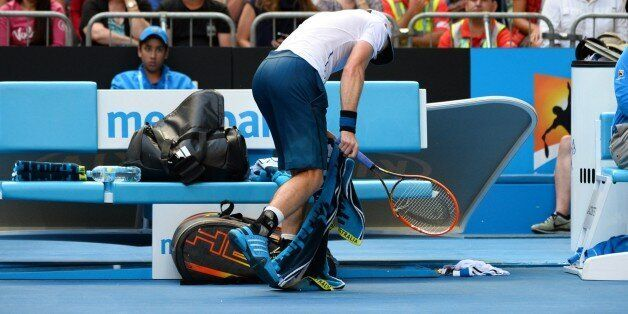 Andy Murray of Britain smashes his racket against the ground during his game against Stephane Robert...