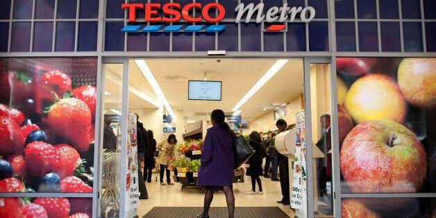 A customer walks into a Tesco Metro