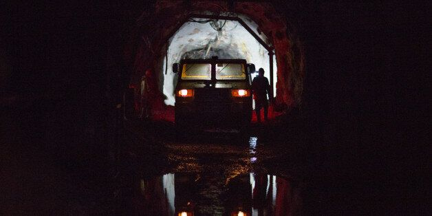 A mine transport vehicle stands ready to collect miners after they finish their shifts in an underground...