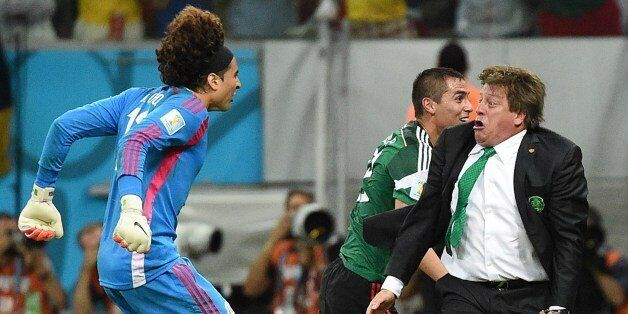 Mexico's goalkeeper Guillermo Ochoa (L) and Mexico's coach Miguel Herrera (R) celebrate a goal by their...